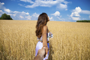 Follow me, Beautiful sexy young woman holds the hand of a man in a wheat field