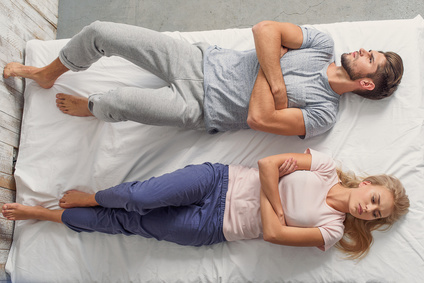 Offended couple is lying on bed with sadness. Man and woman are crossed arms with mistrust