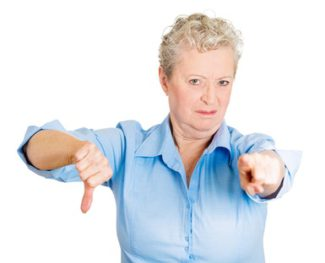 Closeup portrait, sarcastic, senior, mature woman with bad attitude showing thumbs down sign hand, pointing at you, isolated white background. Negative emotion, facial expression feelings