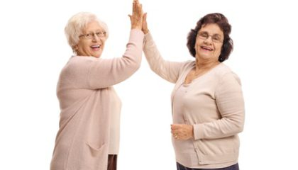 Two elderly women high-fiving each other and looking at the camera isolated on white background